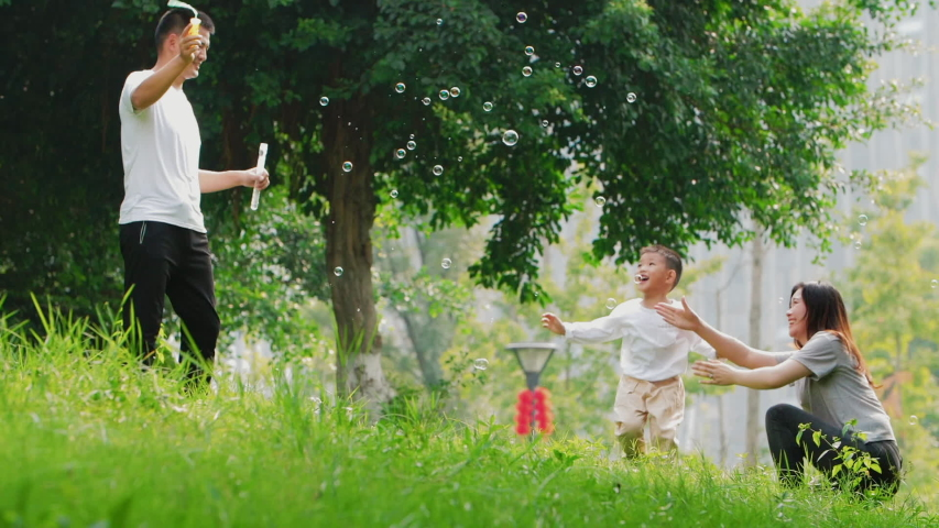 Slow motion happy Chinese family playing outdoor in summer park little Asian boy chasing soap bubble together with parents young couple having fun with son lovely mom dad wellbeing lifestyles nature