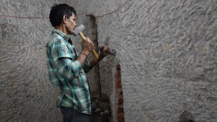 A Man working with a hammer and chisel at an Indian House in New Delhi,India | Shutterstock HD Video #1038516650