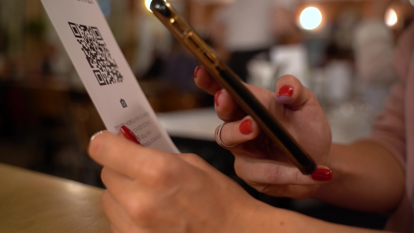 Scanning QR code with smart phone. The woman reads the bar code using the application on the smartphone in cafe