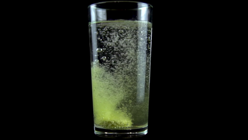 A vitamin C tablet is thrown into a transparent glass glass with water. The effervescent yellow tablet dissolves. Glass on a black background. Slow motion