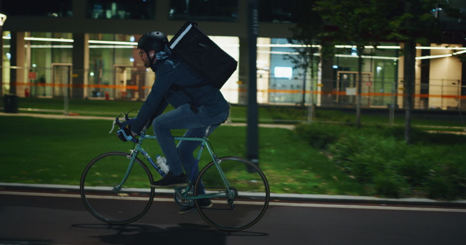 Slow motion of an young courier wearing a security helmet is making a delivery of the order to the customers by bicycle in the evening in a city center. | Shutterstock HD Video #1038527381