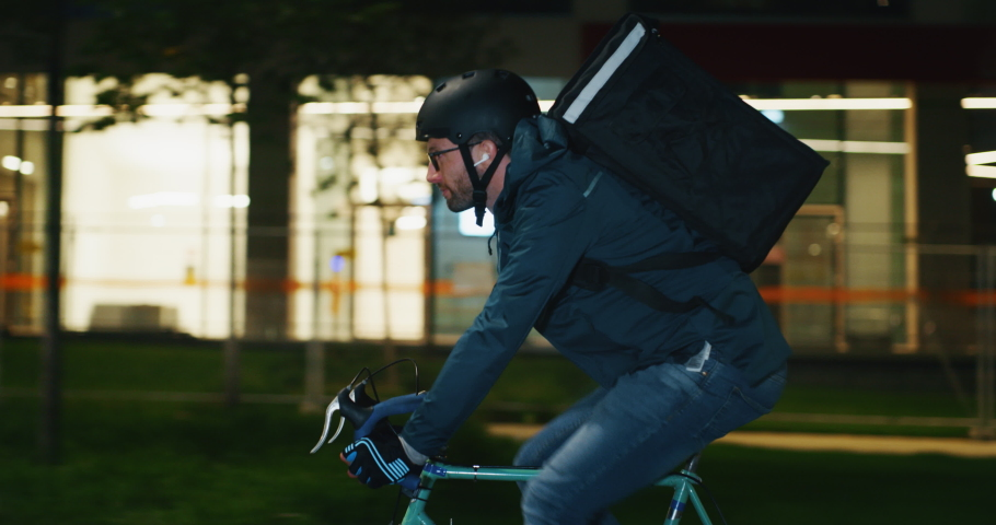 Slow motion of an young courier wearing a security helmet is making a delivery of the order to the customers by bicycle in the evening in a city center. | Shutterstock HD Video #1038527393