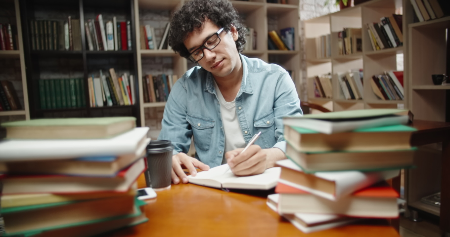 Asian student with curly hair is in library, sits at desk full of books. Guy wearing glasses preparing for exam and studying - education concept close up 4k | Shutterstock HD Video #1038540128