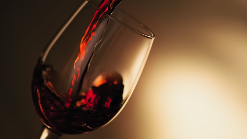 Close-up of filling wine glass with red wine in super slow motion. Pouring red wine into goblet. Red wine forms beautiful wave in glass | Shutterstock HD Video #1038544145