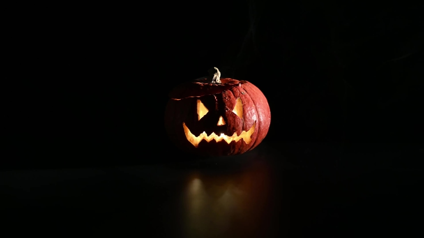 Halloween, orange pumpkin with a scary luminous face on a dark background. Thick gray smoke comes out and spreads across the black table. A close-up of a flashlight on the eve of all the saints | Shutterstock HD Video #1038545267