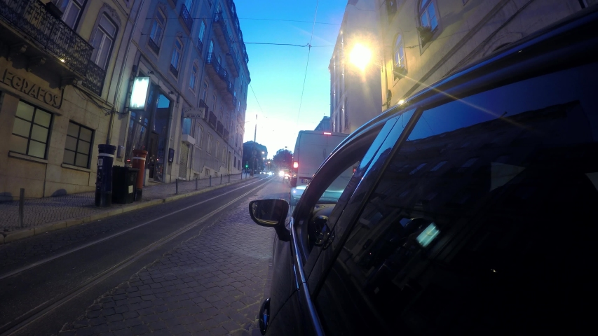Hyperlapse from a moving car driving on Lisbon city center streets Portugal at blue hour