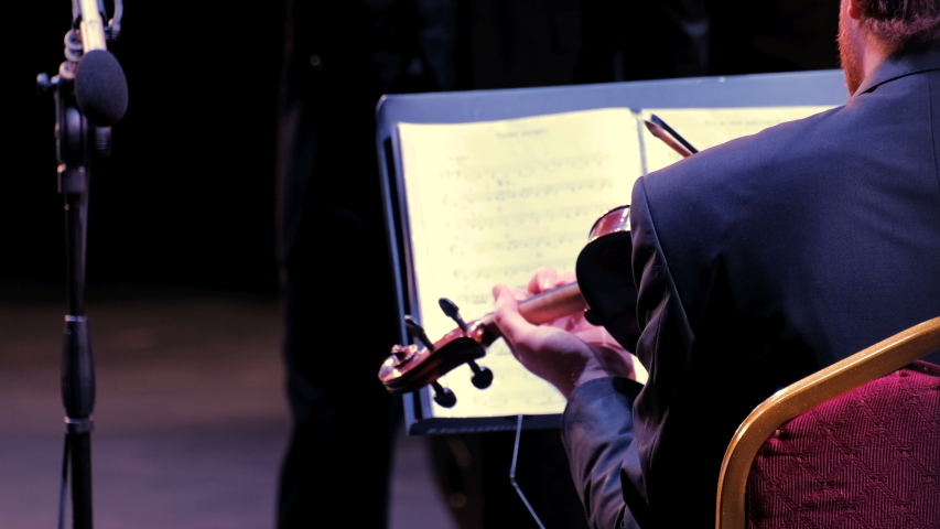 Violinist and conductor. Performance of the municipal symphony orchestra, detail of stringed instruments. Concert of jazz or rock music or opera. Close-up. The view from the back. | Shutterstock HD Video #1038557078