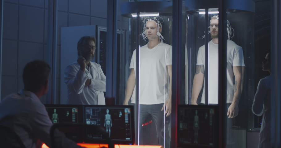 Medium shot of scientists examining two young male astronauts standing in stasis pods while preparing for spaceflight | Shutterstock HD Video #1038562301