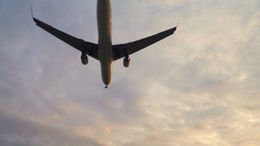 Plane flying overhead in sunset cloudy sky. Aircraft landing in evening slowmo | Shutterstock HD Video #1038565124