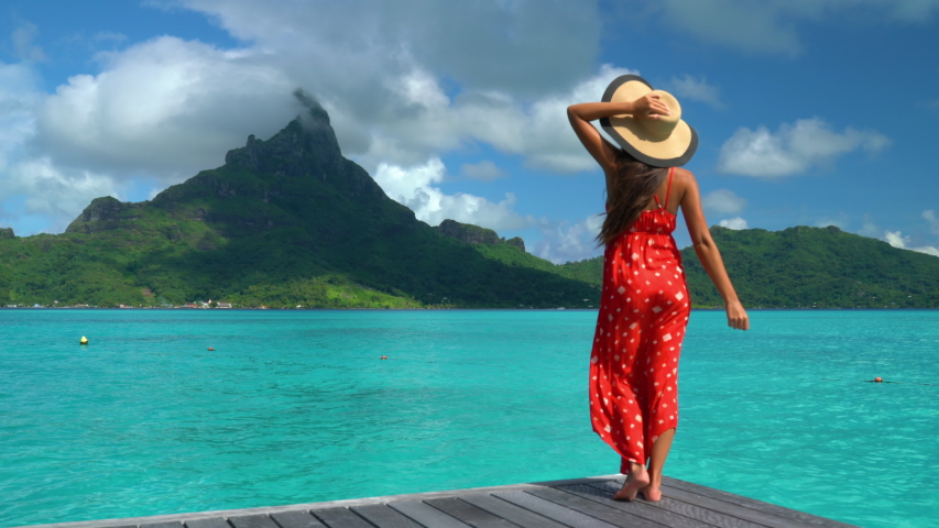 Travel influencer visiting famous destination on Bora Bora. Vacation woman on paradise motu beach on holidays in French Polynesia Girl on luxury travel in overwater bungalow resort hotel in Tahiti.