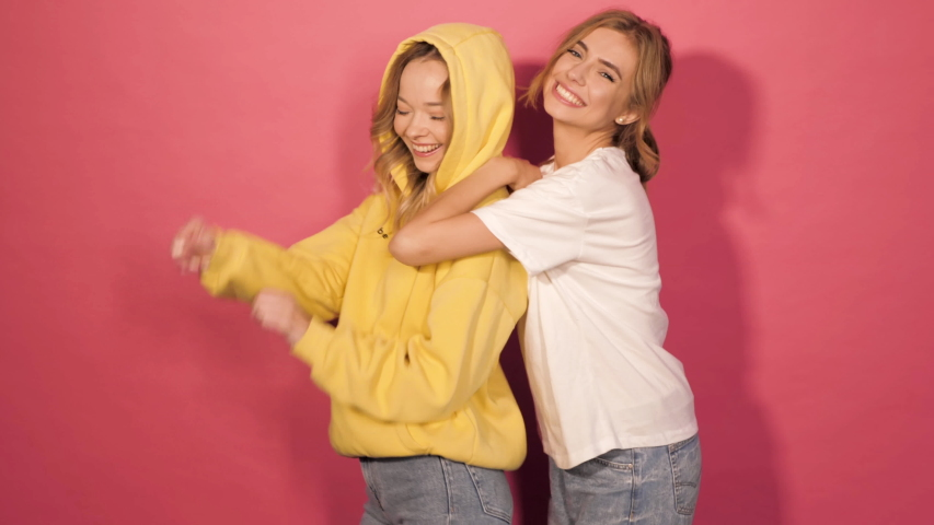 Two young beautiful smiling hipster girls in trendy summer clothes.Sexy carefree women posing in studio near pink wall.Positive models having fun and dance.Showing good relations and hugging.Dancing