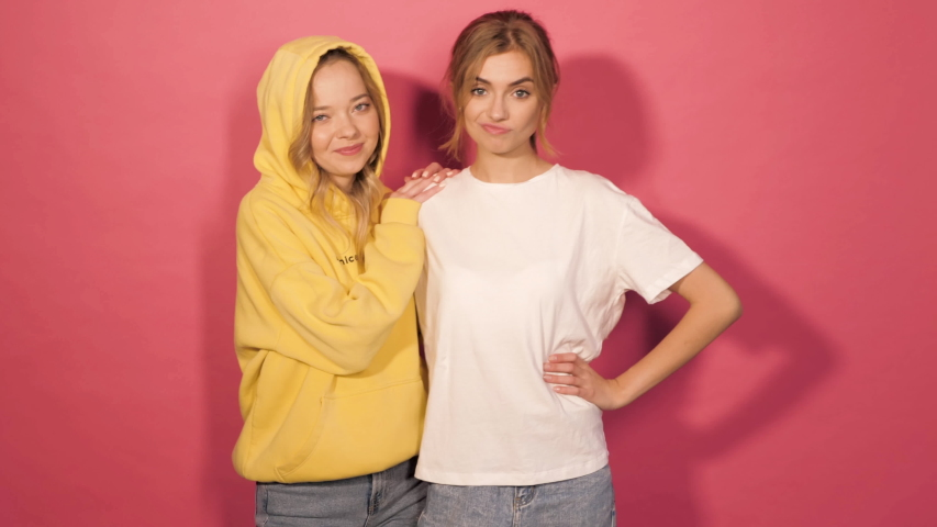 Two young beautiful smiling hipster girls in trendy summer clothes.Sexy carefree women posing in studio near pink wall.Positive models having fun and dance.Showing good relations and hugging