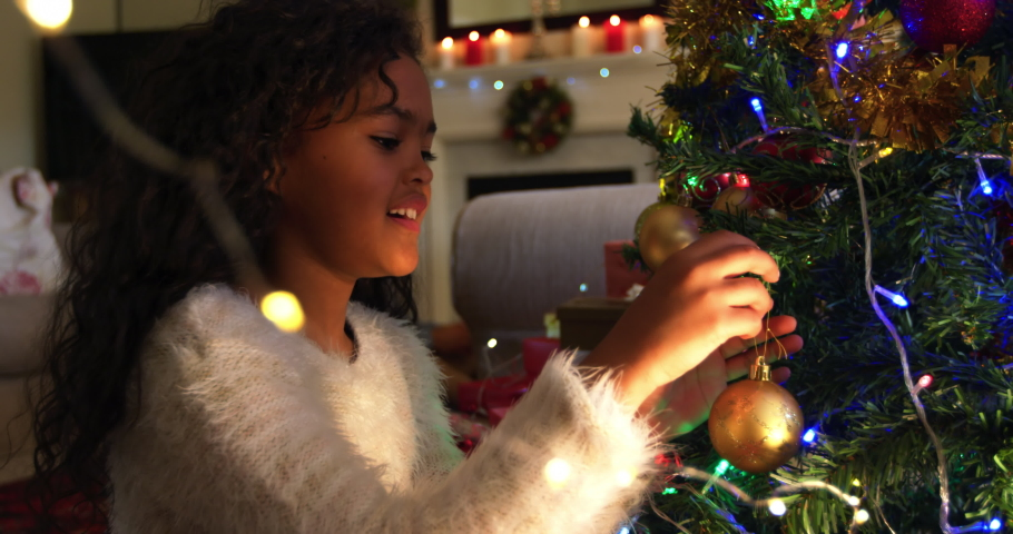 Side view close up of a young mixed race girl in her sitting room at Christmas decorating the Christmas tree and smiling with joy, her father visible sitting in the background