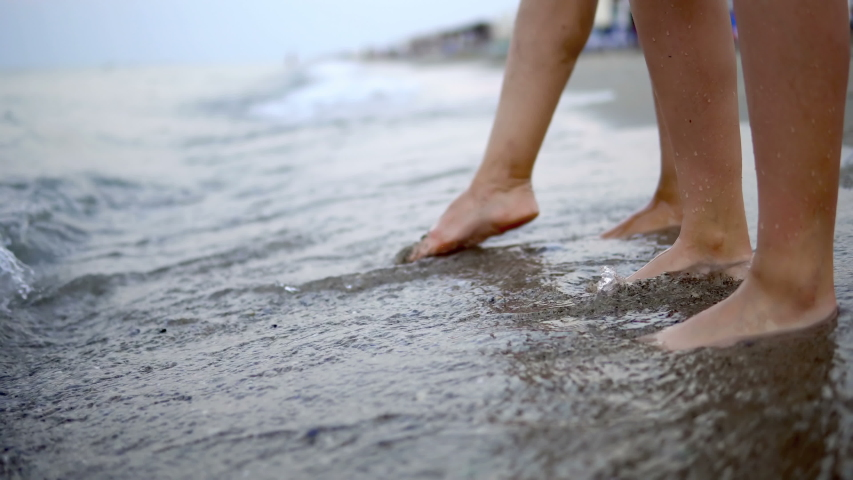 Young couple feet dancing in the sea waves at sunrise | Shutterstock HD Video #1038595793