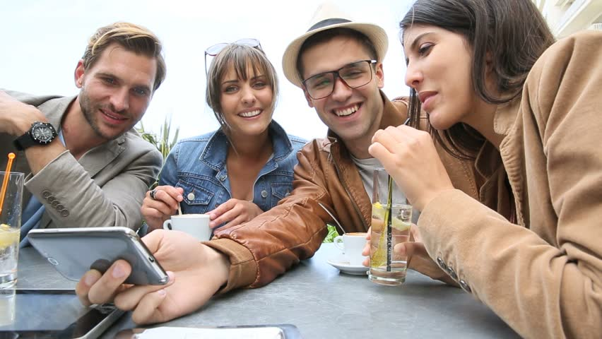Young people at coffee shop table looking at pictures on smartphone #10385984