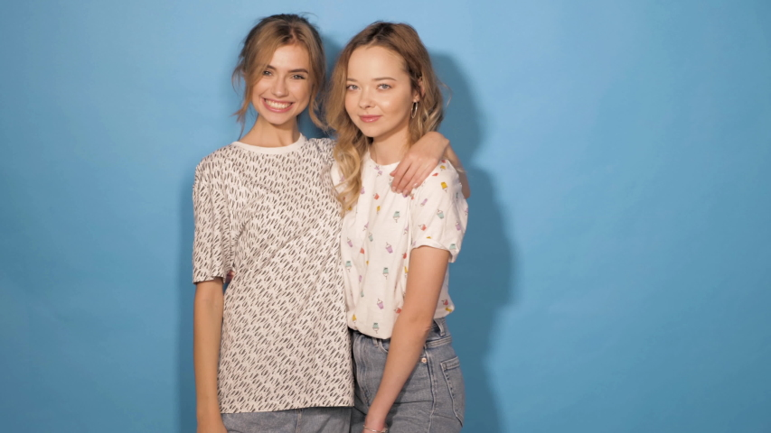 Two young beautiful smiling hipster girls in trendy summer clothes.Sexy carefree women posing in studio near blue wall.Positive models having fun and dance.Shows tongue and winking