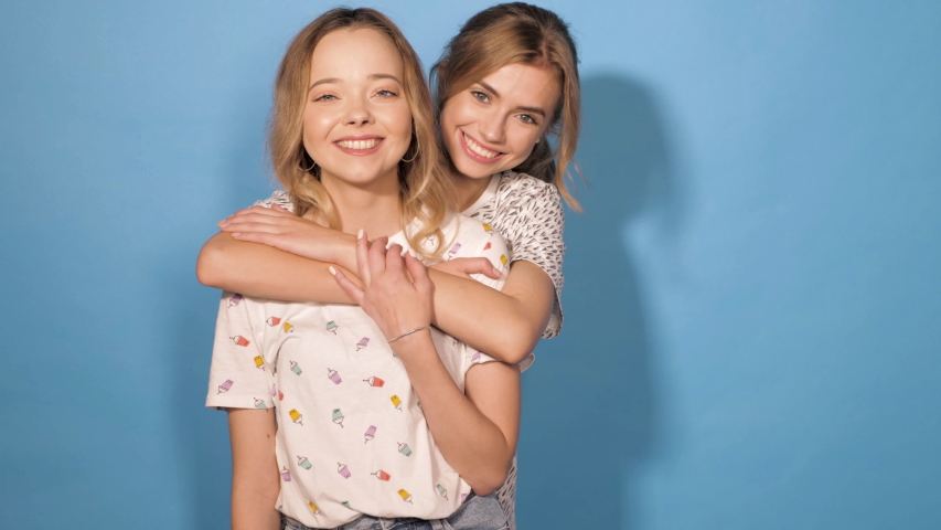 Two young beautiful smiling hipster girls in trendy summer clothes.Sexy carefree women posing in studio near blue wall.Positive models having fun and dance.Shows tongue and winking. Hugging each other