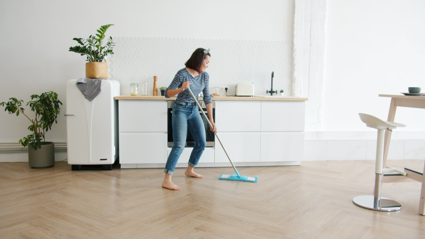 Happy young woman cute housewife is washing floor with mop and dancing at home in kitchen enjoying housework. People, modern lifestyle and youth concept.   Shutterstock HD Video #1038603782