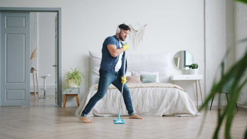 Joyful guy in wireless headphones is singing in mop washing floor at home having fun listening to rock music. Happy people, housework and gadgets concept.