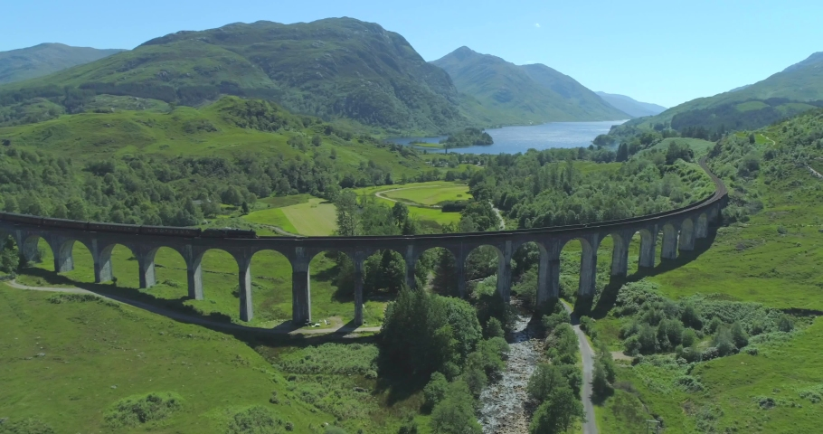 Wide aerial of Hogwart's Express (Harry Potter) steam train travelling over the Glen Finnan Viaduct in the Scottish Highlands with Loch Shiel in the background on a sunny day
