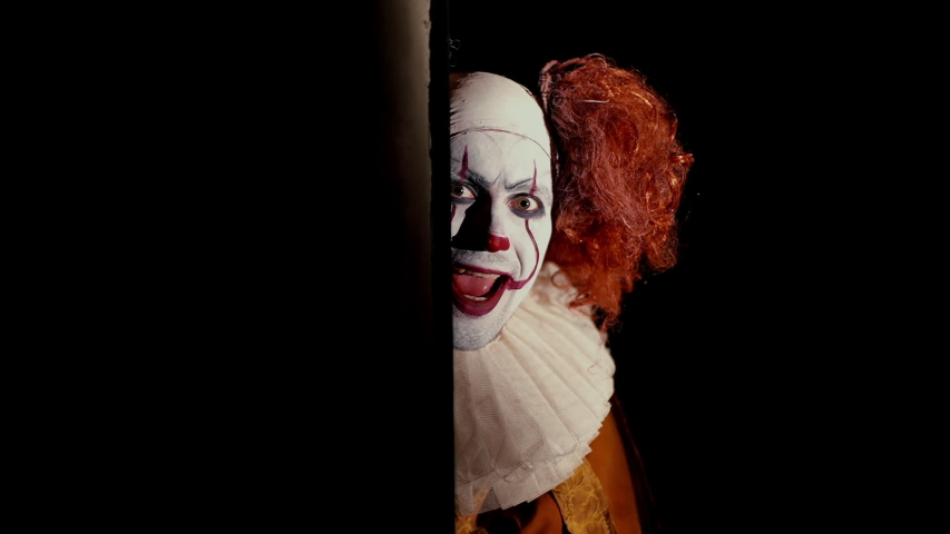 Crazy clown with a wide, frightening smile slowly appears from a dark corner. Shooting in black room, close-up face