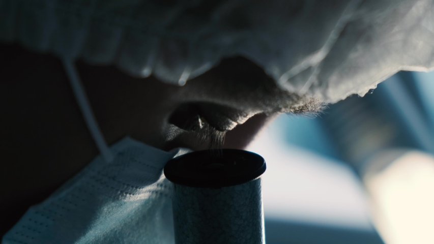 Close-up of a scientist using microscope in a laboratory. Search for coronavirus vaccine