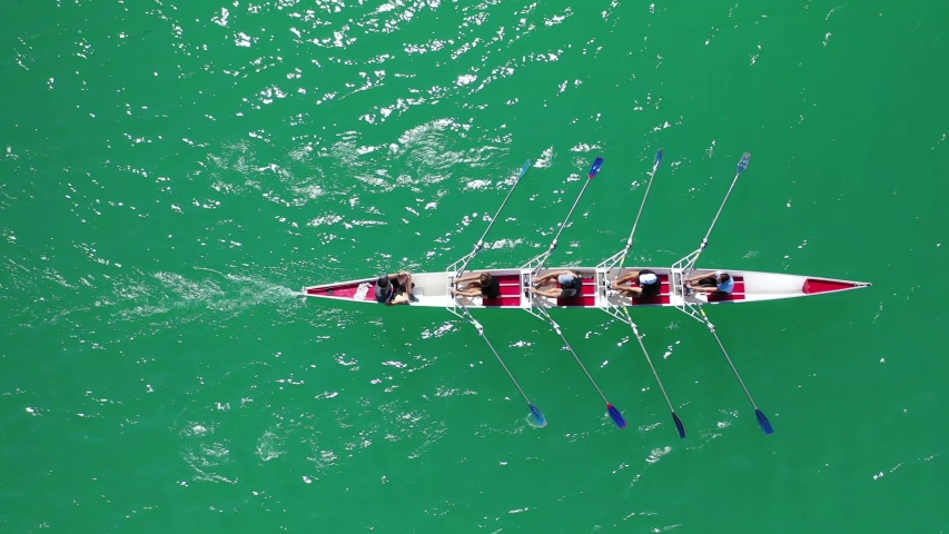 Aerial drone top down view video of sport canoe operated by team of young women in emerald sea | Shutterstock HD Video #1038624881
