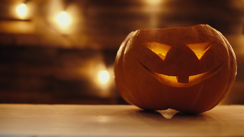 Close-up Halloween pumpkin with burning candle inside in dark room. Holiday Jack-O'-Lantern with scary luminous face on the background of the wall with bright garland. Camera changes focus | Shutterstock HD Video #1038627038