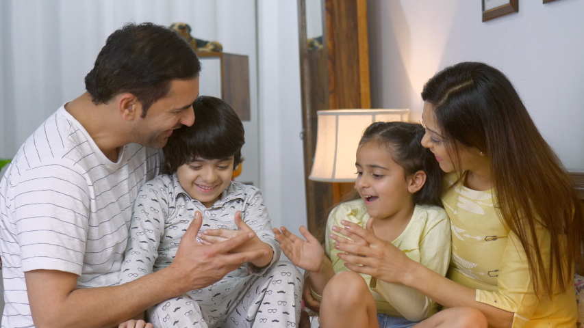 Smiling Indian parents playing with their cute children before going to sleep - playtime in bed. Happy carefree family from India - Young couple sitting together in bed with their son and daughter,...