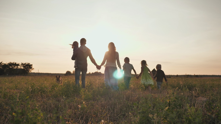 A large family walks along the field at sunset. #1038657995