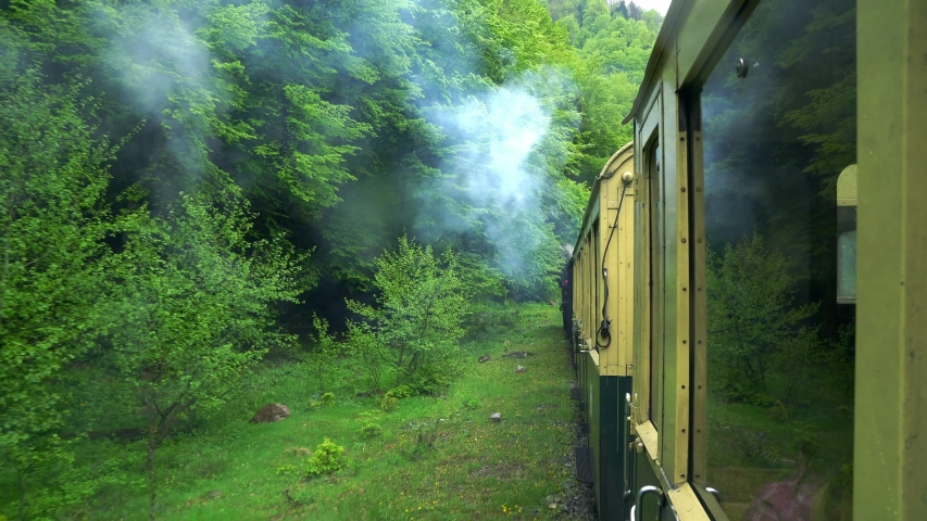 View on mountain river from the window of a retro train wagon, Old steam locomotive in Romania, Steam narrow gauge train, Steam train chugging through the countryside, narrow-gauge railway