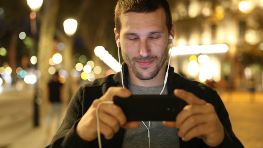 Happy adult man wearing earbuds watching online videos on mobile phone walking towards camera in the street in the night