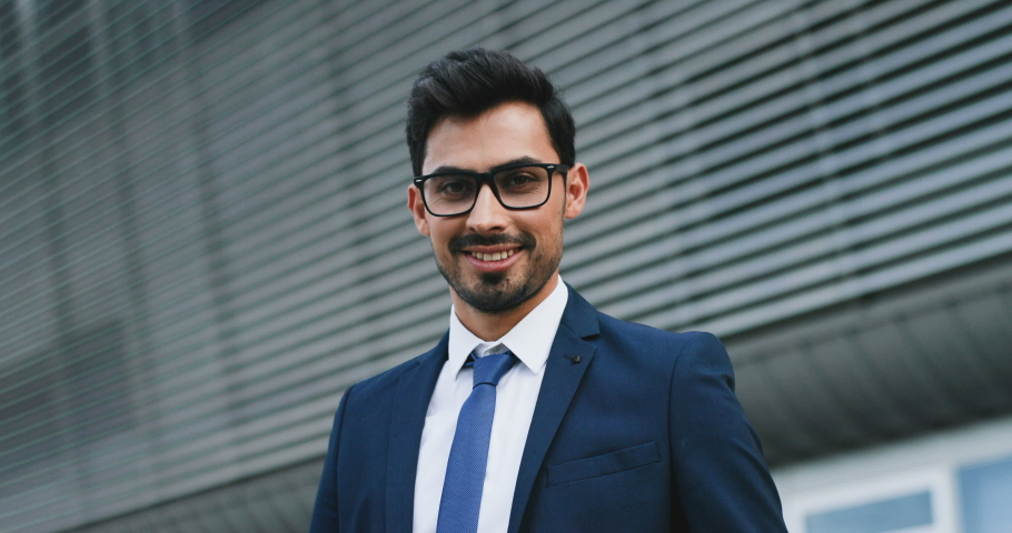 Portrait of the young attractive Arabian man in business style and glasses turning his face to the camera and smiling happily. Close up. Outdoors.