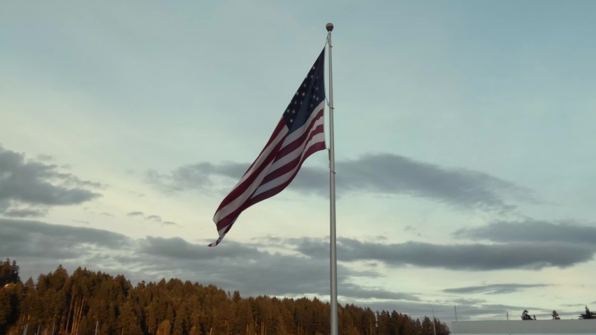American flag waving at the top of a tall flag pole | Shutterstock HD Video #1038692528