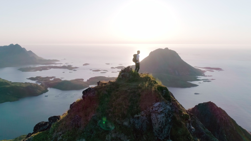 4K drone shot of Norwegian climber standing on the top of a tall mountain looking at and admiring the panorama sunset background view of Lofoten and Vesterålen in Norway.
