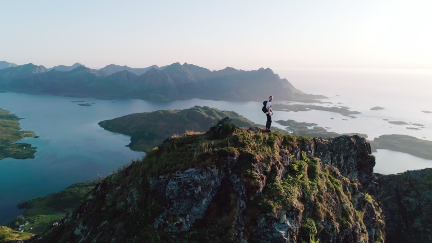 4K drone shot with orbit motion of Norwegian climber standing on the top of a tall mountain looking at and admiring the panorama sunset background view of Lofoten and Vesterålen in Norway. | Shutterstock HD Video #1038701123