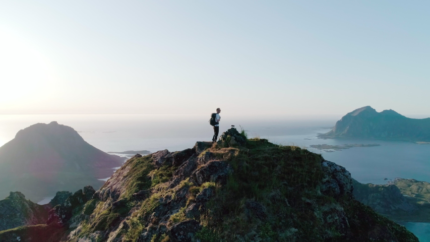 4K drone shot of Norwegian climber standing on the top of tall mountain looking at and admiring the panorama sunset background view of Lofoten and Vesterålen in Norway. | Shutterstock HD Video #1038701132