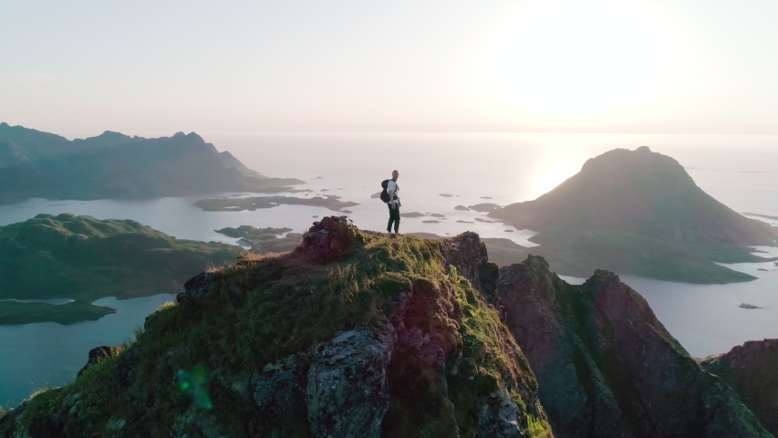 4K drone shot with orbit motion of Norwegian climber celebrating climbing top of a mountain by raising his arms to the sky with panorama sunset background view of Lofoten and Vesterålen, Norway.