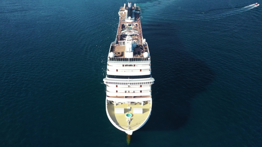 Aerial drone tracking video of huge cruise liner with pools and outdoor facilities cruising the Atlantic blue ocean Royalty-Free Stock Footage #1038708134