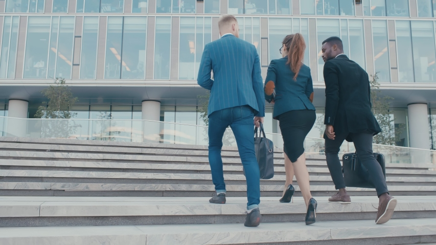 Confident team members walking on stairs in slow motion. Business men and woman in formal suits go and talk on the background of modern office building. Concept of successful employees white collars