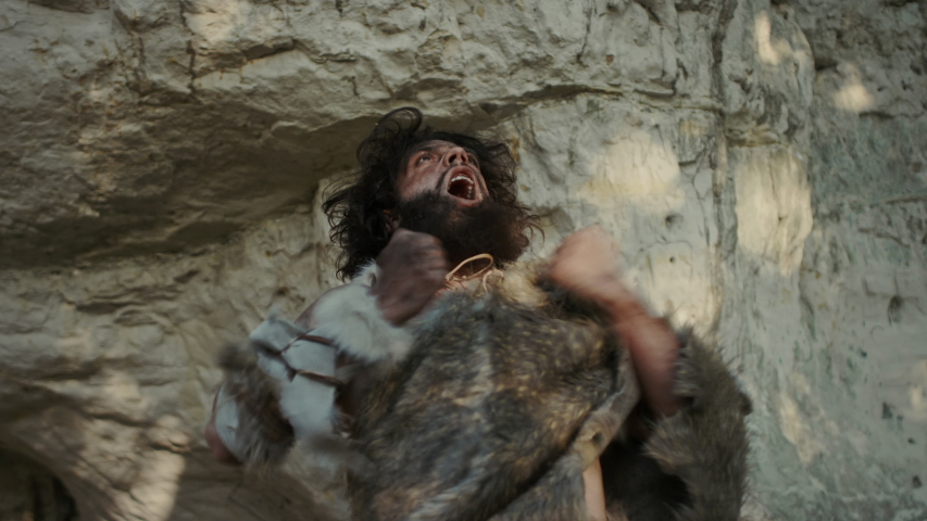 Portrait of Primeval Caveman Wearing Animal Skin Does Aggressive Chest Beating and Screaming, Defending His Cave and Territory in the Prehistoric Forest. Prehistoric Neanderthal or Homo Sapiens Leader Royalty-Free Stock Footage #1038726959