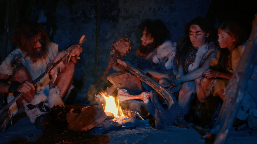 Neanderthal or Homo Sapiens Family Cooking Animal Meat over Bonfire and then Eating it. Tribe of Prehistoric Hunter-Gatherers Wearing Animal Skins Grilling and Eating Meat in Cave at Night Royalty-Free Stock Footage #1038726965