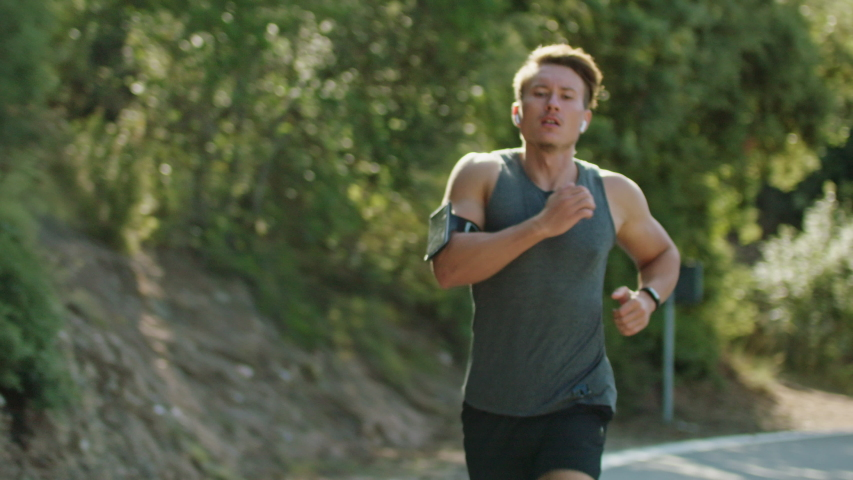 Young athlete man running on the road in the morning listens to music wearing fitness tracker, fitness cross training, intense workout challenge training endurance in the mountains, Slow Motion | Shutterstock HD Video #1038727499