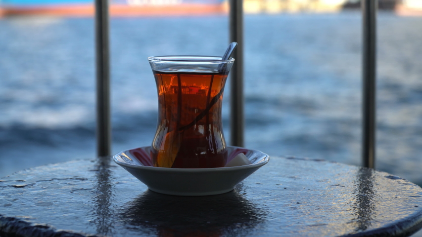 Reflection of the city in a turkish tea glass at a ferry when on the move | Shutterstock HD Video #1038729023