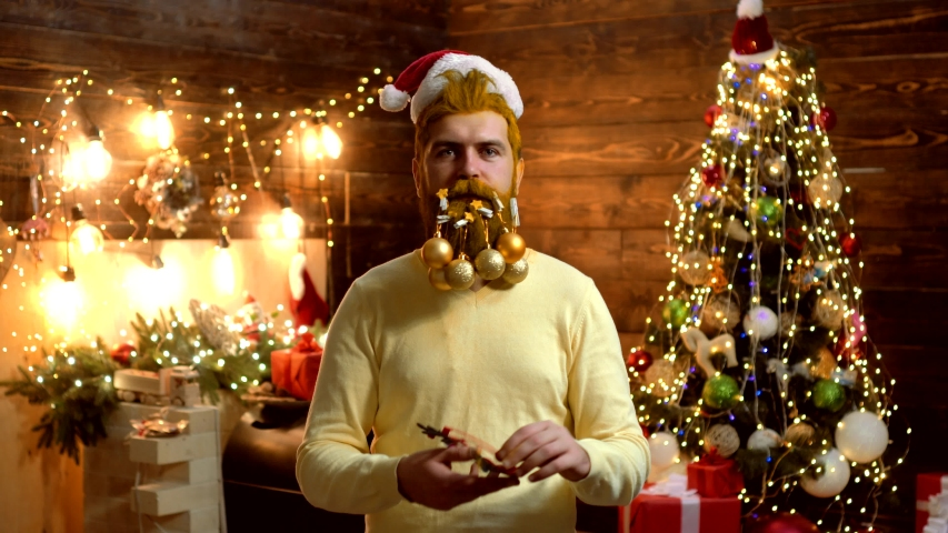 Hipster Santa Claus Christmas preparation. Attractive bearded hipster. Christmas Celebration. Christmas party. Christmas man in Santa hat. Portrait of surprised and funny man. Santa fun | Shutterstock HD Video #1038732488