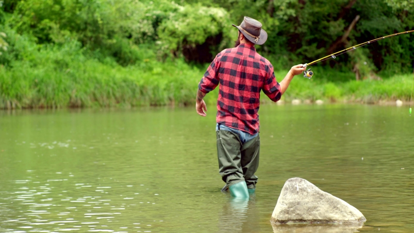 Fisherman with fishing rod on the river. Brown trout fish. Summer holidays and people concept. Trout on a hook. Holding brown trout. Fly fishing for trout