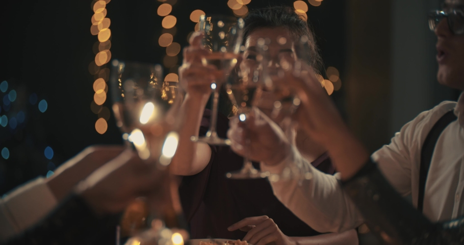 Multiracial young mans and womans wearing fashion wear clinking glasses with champagne, happy asian american and caucasian friends celebrating xmas, new year or birthday party indoors