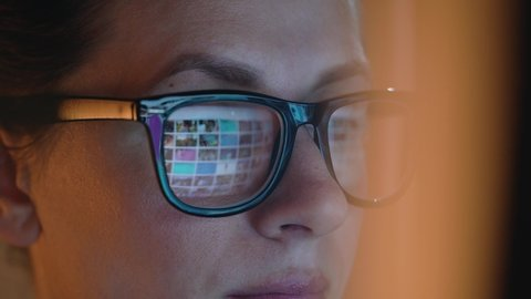 Woman in glasses looking on the monitor and surfing Internet. The monitor screen is reflected in the glasses