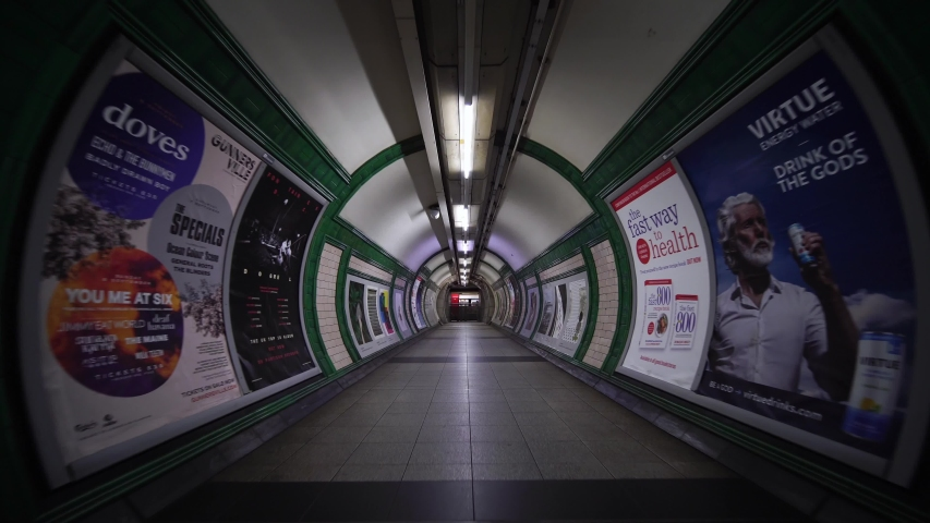 LONDON, ENGLAND - SEPTEMBER 10, 2019:  Tunnel path for commuters and city workers in London tube underground subway train station. Concept of English modern urban life, city lifestyle in England.