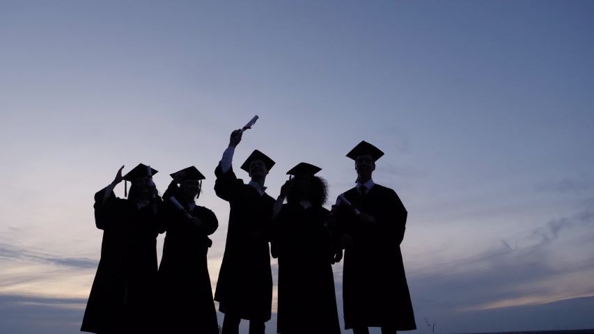 Silhouette of Graduating Students Throwing Caps In The Air. Royalty-Free Stock Footage #1038761039